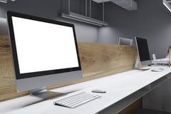 Het witte computerscherm in een grijs bureau Royalty-vrije Stock Foto's