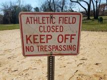 Het witte en rode atletische gesloten gebied houdt geen het schenden teken op vuil op een afstand stock fotografie