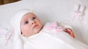 Het witte gebreide jasje van het babymeisje met roze konijn stock video