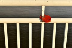Het witte geschilderde traliewerk van de dijk van de rivier Met een rood hart-vormig slot dat op een metaalpijp wordt gesloten royalty-vrije stock afbeeldingen
