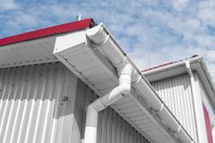 Het witte guttering op een huis met rood dak tegen blauwe hemel Plastic guttering systeem De pijpbuitenkant van de Gutteringsdrai royalty-vrije stock fotografie