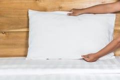 Het witte hoofdkussen van de handopstelling op bedblad in hotelruimte Stock Afbeelding
