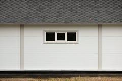 Het witte huis van de muurtextuur, donkere doos, flexibele bruine tegels op de achtergrond van multi-colored bos van de bladerenh Royalty-vrije Stock Foto