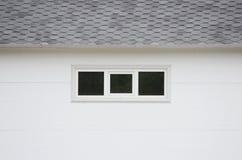 Het witte huis van de muurtextuur, donkere vensters, flexibele grijze tegelsachtergrond Stock Afbeeldingen