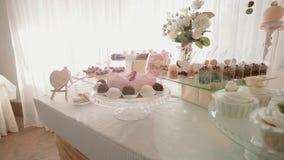 Het witte Huwelijk van de Suikergoedbar, huwelijksgebakjes op het zoete buffet van het lijstsuikergoed Bewegingscamera stock videobeelden