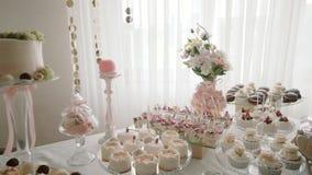 Het witte Huwelijk van de Suikergoedbar, huwelijksgebakjes op het zoete buffet van het lijstsuikergoed Bewegingscamera Midleschot stock footage