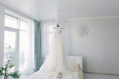 Het witte huwelijkskleding hangen in de slaapkamer Witte bruidkleding royalty-vrije stock fotografie