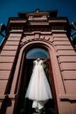 Het witte huwelijkskleding hangen in de slaapkamer Witte bruidkleding royalty-vrije stock foto's