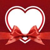Het witte kader van de hartgrens met rode lintboog op rood Stock Afbeelding