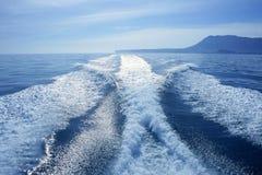 Het witte kielzog van de boot op het blauwe oceaanoverzees stock foto's