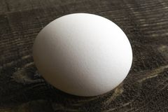 Het witte kippenei legt op bruine houten lijst stock fotografie