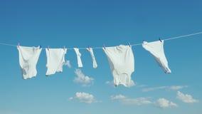 Het witte linnen droogt op de kabel tegen de blauwe hemel stock fotografie