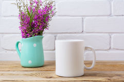 Het witte model van de koffiemok met kastanjebruine purpere bloemen in munthoogte Royalty-vrije Stock Foto