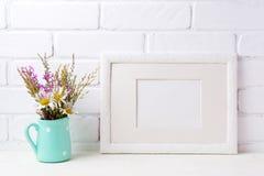 Het witte model van het landschapskader met kamille en purpere bloemen i Stock Foto
