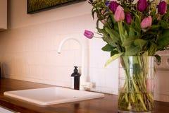Het witte moderne binnenland van de keukengootsteen met bloemstruik Royalty-vrije Stock Foto