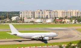 Het witte passagiersvliegtuig beweegt zich langs de taxibaan en wordt klaar op te stijgen Stock Fotografie