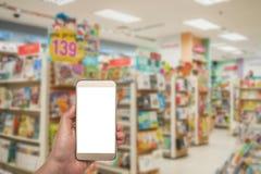 Het witte scherm van Smartphone ter beschikking op vage boekhandel Royalty-vrije Stock Foto's
