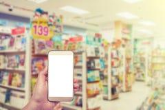 Het witte scherm van Smartphone ter beschikking op vage boekhandel Stock Afbeelding