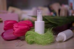 Het witte schoonheidsmiddel van de nevelfles op de achtergrond van het tulpenonduidelijke beeld stock foto