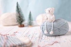 Het witte stuk speelgoed draagt zit op lichtblauwe bal van garen Stock Afbeelding