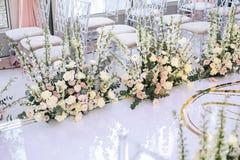 Het witte tapijt voor de huwelijksceremonie is verfraaid met bloemsamenstellingen van rozen, boterbloem en klokken met transparan royalty-vrije stock afbeeldingen
