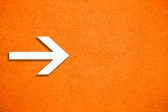 Het witte teken van de pijlrichting over de levendige heldere oranje ruwe muur van de kleurengipspleister als lege rustieke en ee stock fotografie