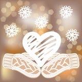 Het witte uitbroedende hart en de gebreide vuisthandschoenen op vage achtergrond met schitteren en sneeuwvlokken Stock Foto