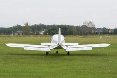 Het witte vliegtuig landde op een gazon Stock Foto's