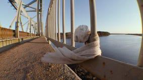 Het witte vod hangen los op de omheining van de brug stock video