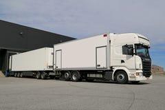 Het witte Volledige de Aanhangwagen van Scania R560 Leegmaken bij een Pakhuis Stock Foto's