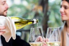 Het witte wijn gieten met paar op achtergrond stock fotografie