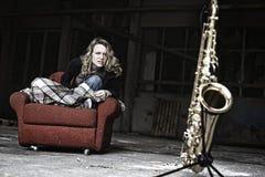Het woedende meisje starring bij saxofoon stock foto