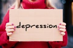 Het woord 'depressie 'in de handen van een meisje op de straat, op een kartonplaat die worden geschreven stock fotografie