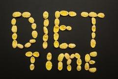 Het woord 'dieettijd 'van cornflakes op een zwarte achtergrond stock afbeelding