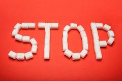 Het woord 'einde 'van kubussen van suiker op een rode achtergrond royalty-vrije stock afbeeldingen