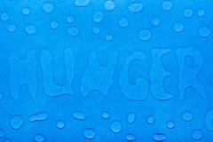 Het woord 'honger 'wordt geschreven met waterdruppeltjes en waterdruppeltjes op een blauwe vlotte oppervlakte royalty-vrije stock foto