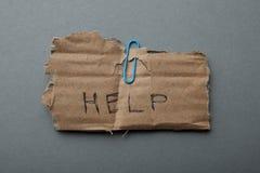 Het woord 'hulp 'op karton wordt, op een grijze achtergrond, een armoede en een wanhoop wordt geïsoleerd geschreven die royalty-vrije stock afbeeldingen