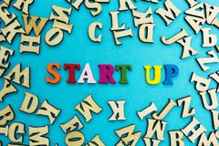 Het woord 'opstarten 'wordt opgemaakt van multicolored brieven op een blauwe achtergrond royalty-vrije stock afbeeldingen