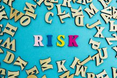 Het woord 'risico 'wordt opgemaakt van multicolored brieven op een blauwe achtergrond Verspreide houten brieven stock foto
