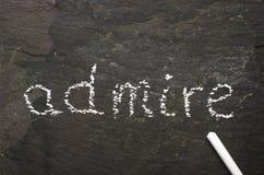 Het woord bewondert geschreven met krijt op zwarte steen Stock Foto