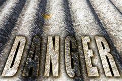 Het woord` gevaar ` met brieven wordt geschreven die de achtergrond die van de asbestgrafiek hebben royalty-vrije stock fotografie