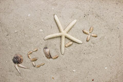 Het woord ONTSPANT op zandig strand Stock Foto's