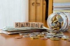 Het woord van de geldbesparing met muntstukken en bankbiljetten Stock Afbeelding