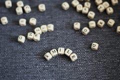 Het woord van de titelglimlach op een grijze stoffenachtergrond stock foto's