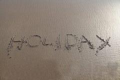 Het woord van de vakantie in zand wordt geschreven dat Royalty-vrije Stock Foto