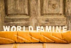 Het woord van de wereldhongersnood op baguette met houten achtergrond stock afbeeldingen