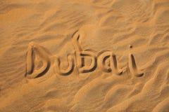 Het woord van Doubai in zandwoestijn stock afbeelding