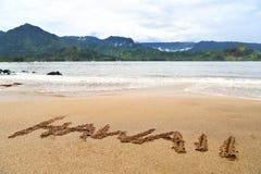 Het woord van Hawaï dat op zand op Hawaiiaans strand wordt geschreven royalty-vrije stock afbeelding