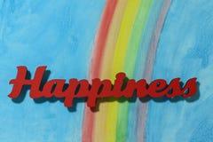 Het woordgeluk met een kleurrijke regenboog en een blauwe hemelachtergrond Royalty-vrije Stock Afbeeldingen