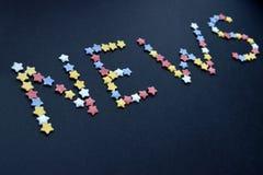Het woordnieuws wordt geschreven door dun type van de sterren van het suikergebakje op een blauwe achtergrond, voor reclame, hand royalty-vrije stock afbeeldingen